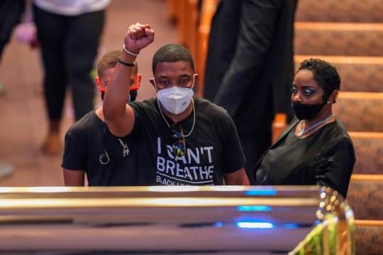 Un homme lève le poing alors qu'il regarde le cercueil de George Floyd lors d'une visite publique le lundi 8 juin 2020, à l'église The Fountain of Praise à Houston. Floyd est décédé après avoir été retenu par des policiers de Minneapolis le 25 mai. (Photo de Godofredo A. VASQUEZ / POOL / AFP) (Photo de GODOFREDO A. VASQUEZ / POOL / AFP via Getty Images)