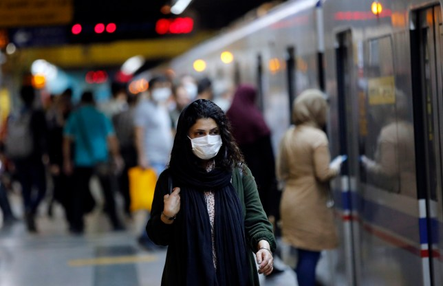 An Iranian woman wearing a face mask takes a train in a subway station