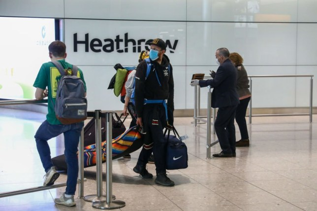 Passengers, wearing protective face masks, walk through the international arrivals hall after arriving at Terminal 2 at London Heathrow Airport