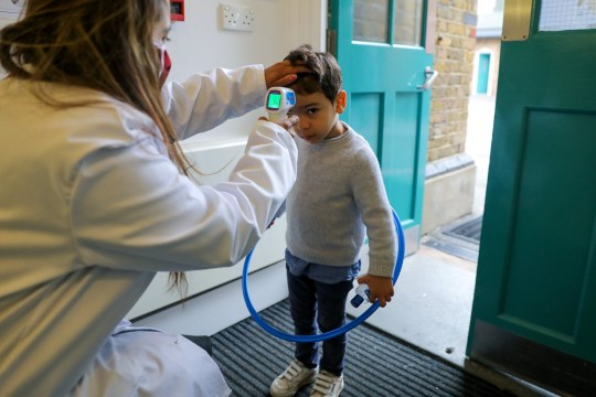 A child has his temperature checked on arrival at L'Ecole de Battersea, an independent French bilingual school, as the coronavirus disease (COVID-19) lockdown eases in Battersea, London, Britain, June 11, 2020.