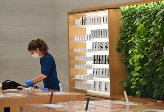 Workers wearing PPE (personal protective equipment) of a face mask and gloves as a precautionary measure against COVID-19, clean and prepare display surfaces inside the Apple store on Oxford Street in central London on June 11, 2020, as non-essential shops prepare to re-open on June 15. - Britain's current guidelines on social distancing remain at two metres (2M), but business leaders and some politicians are on Thursday calling for it to be reduced to one (1M), or one-and-a-half (1.5M) metres. All non-essential shops in England have been told they could re-open from June 15, as long as they comply with health and safety guidelines. (Photo by JUSTIN TALLIS / AFP) (Photo by JUSTIN TALLIS/AFP via Getty Images)