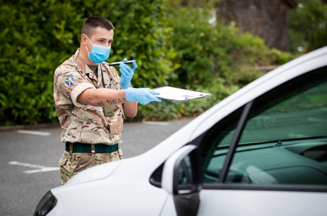 A member of the 5th Battalion Royal Regiment of Scotland Balaclava Company working at a mobile coronavirus testing unit