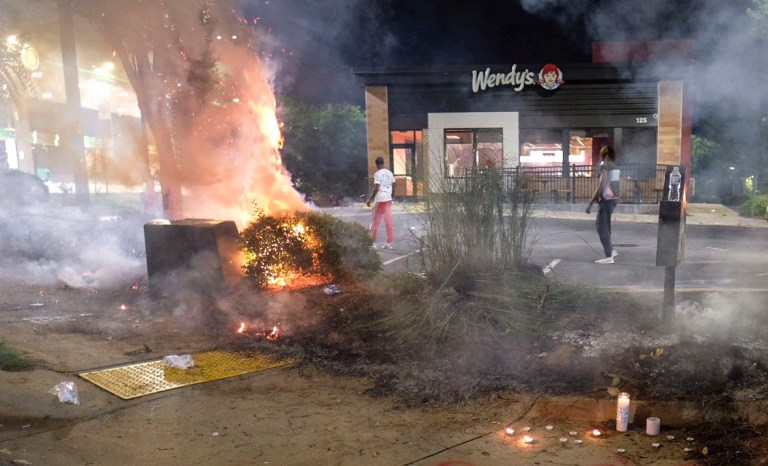 A Wendy's restaurant, background, burns Saturday, June 13, 2020, in Atlanta after demonstrators set it on fire. Demonstrators were protesting the death of Rayshard Brooks, a black man who was shot and killed by Atlanta police Friday evening following a struggle in the Wendy's drive-thru line.