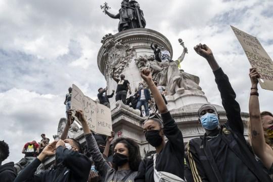 Les manifestants se tiennent sur le monument de la Place de la République lors d'une manifestation contre le racisme le 13 juin 2020 à Paris, France