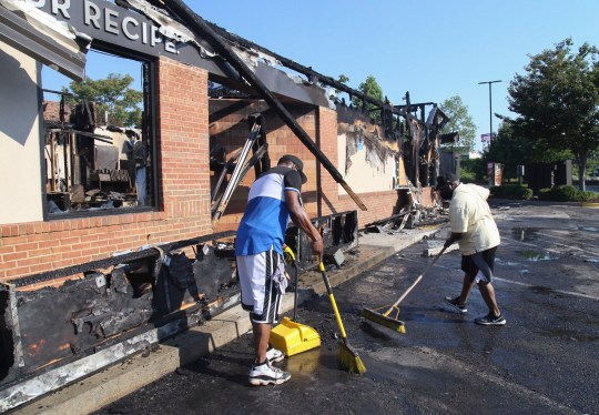 Renault Verona, left, and other area residents clean up the site Sunday, June 14, 2020 where protestors on Saturday set fire to the Atlanta Wendy's where Rayshard Brooks, a 27-year-old Black man, was shot and killed by Atlanta police Friday evening during a struggle in a Wendy's drive-thru line. (Steve Schaefer/Atlanta Journal-Constitution via AP)