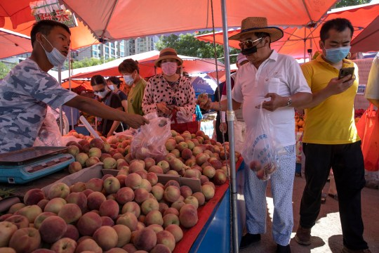 Residents wearing face masks to curb the spread of the coronavirus shop for fruit at an open air market in Beijing, Monday, June 15, 2020. China's capital was bracing Monday for a resurgence of the coronavirus after more than 100 new cases were reported in recent days in a city that hadn't seen a case of local transmission in more than a month. (AP Photo/Ng Han Guan)