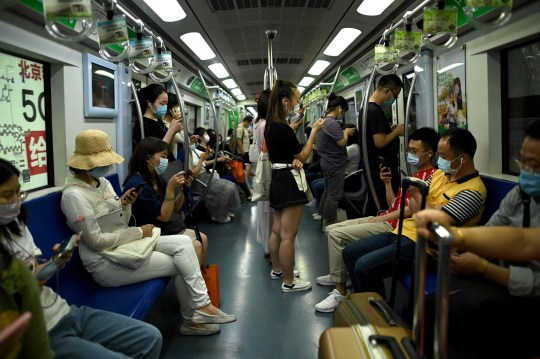 Passengers wearing face masks commute on a subway train during rush hour in Beijing on June 15, 2020