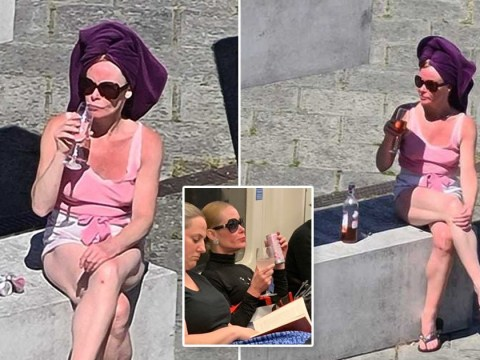 Iconic 'Pink Gin Lady' seen sipping rosé in the sun with a towel on her head