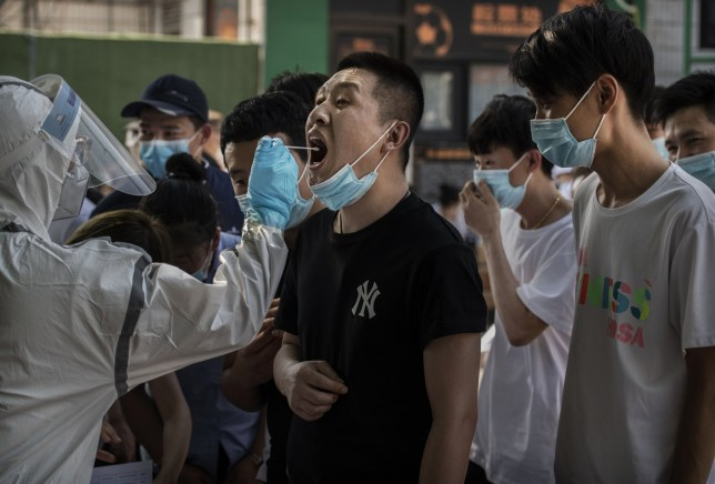 BEIJING, CHINA - JUNE 16: A Chinese man who has had contact with the Xinfadi Wholesale Market or someone who has, reacts as a Chinese epidemic control worker performs a nucleic acid test for COVID-19 at a testing center on June 16, 2020 in Beijing, China. Authorities are trying to contain the outbreak linked to the Xinfadi wholesale food market, Beijing's biggest supplier of produce and meat. Several neighborhoods have been locked down and at least two other food markets were closed, as tens of thousands of people are being urged to get tested for COVID-19 at sites set up around the city. The outbreak has triggered fears of a second wave of infection after 56 straight days with no domestically transmitted cases in the capital. More than 8,000 vendors and staff at Xinfadi have already been tested, according to city officials, who are using contact tracing to reach an estimated 200,000 people who have visited the market since May 30. (Photo by Kevin Frayer/Getty Images)
