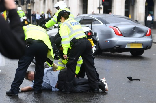 Police detain a man after he ran in front of Prime Minister Boris Johnson's car as it left the Houses of Parliament, Westminster. The man, who had been demonstrating about Turkey's operation against Kurdish rebels in northern Iraq, was taken into the Palace of Westminster by officers. PA Photo. Picture date: Wednesday June 17, 2020. Photo credit should read: Victoria Jones/PA Wire