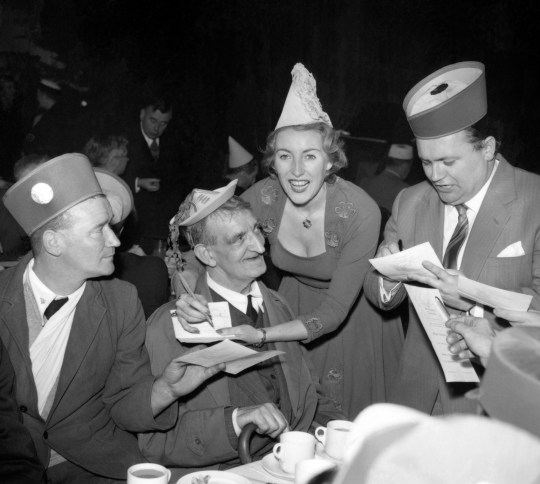 File photo dated 13/12/56 of the singer Vera Lynn, and comedian Harry Secombe (right) signing autographs at the tea tables during the 'don't forget the Association's Christmas party at the Royal Riding School, Buckingham Palace. Forces sweetheart Dame Vera Lynn has died at the age of 103 years. PA Photo. Date of publication: Thursday 18 June 2020. See PA story of the DEATH of Vera. Photo credit should read: PA Wire