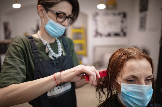 Hairdresser and customer in a salon with medical masks during virus pandemic.