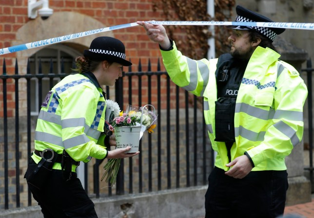 Police officers collect flowers left at the Abbey gateway of Forbury Gardens, Reading