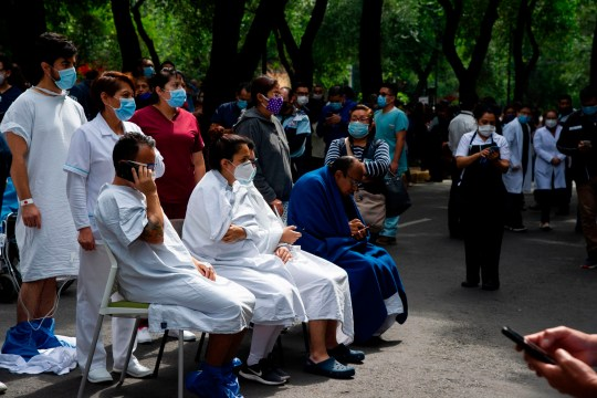 People remain outside the Durango clinic in Mexico City during a quake on June 23, 2020 amid the COVID-19 novel coronavirus pandemic. - A 7.1 magnitude quake was registered Tuesday in the south of Mexico, according to the Mexican National Seismological Service. (Photo by CLAUDIO CRUZ / AFP) (Photo by CLAUDIO CRUZ/AFP via Getty Images)