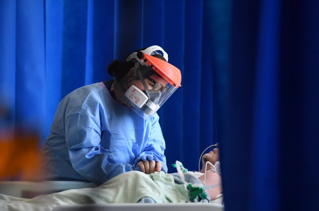 TOPSHOT - A member of the clinical staff wears personal protective equipment (PPE) as she cares for a patient at the Intensive Care unit at Royal Papworth Hospital in Cambridge, on May 5, 2020. - NHS staff wear an enhanced level of PPE in higher risk areas such as critical care to minimise the spread of infection between staff and patients. Britain's death toll from the novel coronavirus COVID-19 has topped 32,000, according to an updated official count released Tuesday, pushing the country past Italy to become the second-most impacted after the United States. (Photo by Neil HALL / POOL / AFP) (Photo by NEIL HALL/POOL/AFP via Getty Images)