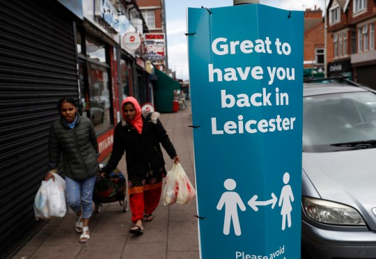 LEICESTER, ENGLAND - JUNE 28: Shoppers walk past a social distancing sign in the North Evington area on June 28, 2020 in Leicester, England. In a television appearance on Sunday, British Home Secretary Priti Patel confirmed the government was considering a local lockdown after a spike in coronavirus cases in the city. (Photo by Darren Staples/Getty Images)