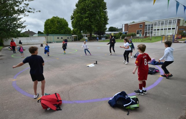 Children dance on a measured and painted socially distanced circle in the playground as they wait to be picked up by their parents at Llanishen Fach Primary School in Cardiff. PA Photo. Picture date: Monday June 29, 2020.