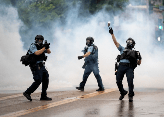 Photo of cops throwing tear gas cannisters