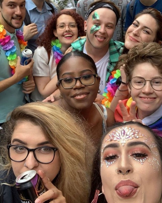 Jay with friends wearing colourful clothes, leis and face paint at Pride in 2019