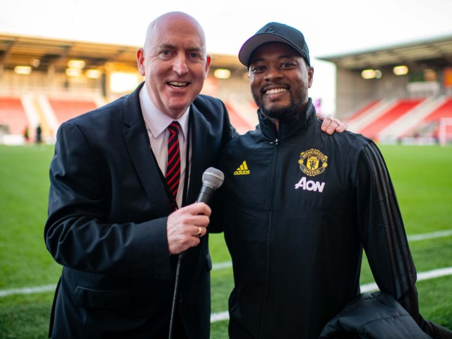 Old Trafford stadium announcer Alan Keegan poses with Patrice Evra ahead of the Barclays FA Women's Super League match between Manchester United and Arsenal at Leigh Sports Village on September 16, 2019 in Leigh, United Kingdom.