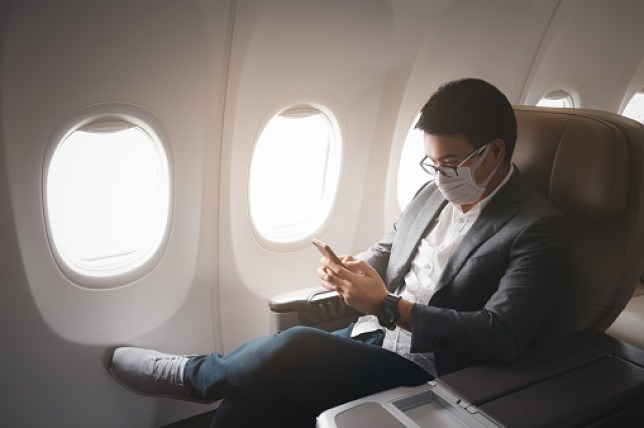 businessman wearing protective face mask on plane