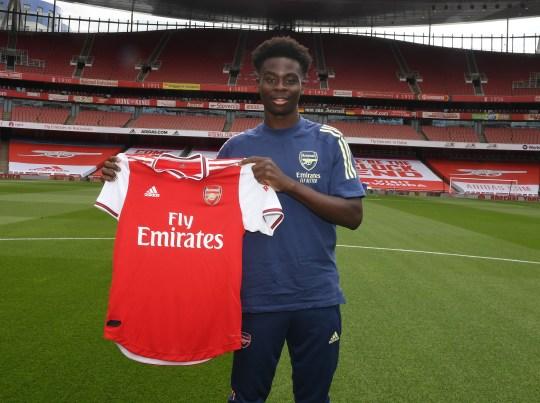 Bukayo Saka poses with an Arsenal shirt at the Emirates