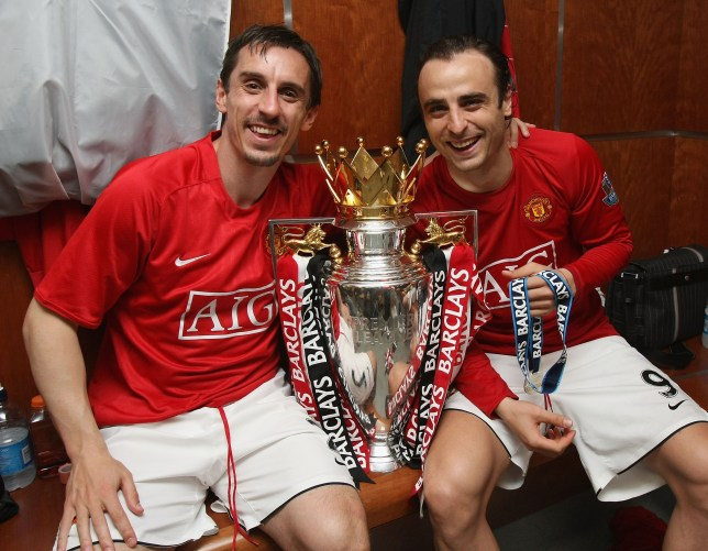 Gary Neville and Dimitar Berbatov of Manchester United celebrates with the Premier League trophy in the dressing room after the Barclays Premier League match between Manchester United and Arsenal at Old Trafford on May 16 2009 in Manchester, England.