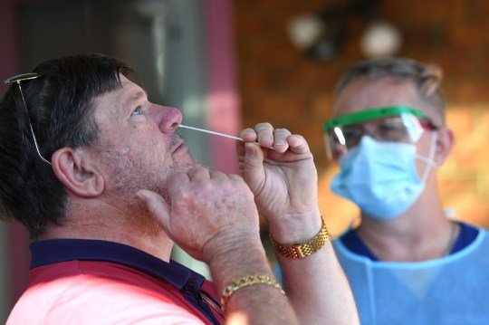 epa08519368 A man carries out his own swab tests for COVID-19 after people displayed cold and flu symptoms, at a private residence in Hallam, Melbourne, Australia, 01 July 2020. Victoria has recently witnessed a spike in coronavirus infections. EPA/JAMES ROSS AUSTRALIA AND NEW ZEALAND OUT