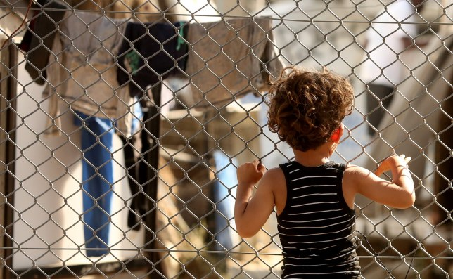 MYTILENE, GREECE - MAY 20: A refugee child looks through a fence at the Moria refugee camp on May 20, 2018 in Mytilene, Greece. Despite being built to hold only 2,500 people, the camp on the Greek island of Lesbos is home to over 6,000 asylum seekers who crossed the Aegean Sea from Turkey's nearby shore by boat, usually at night to avoid interception. Although the numbers of arrivals are lower than at the beginning of the crisis in 2015, when Syrians and Iraqis fled ISIS-controlled strongholds, boatloads of refugees from those countries and other troubled areas continue to land there, and critics say the local governments have yet to manage the situation, leading the squalid conditions at Moria to be seen as symbolic of poorly-managed policy. The camp, on the site of a former military base, is comprised of shipping containers, tents, and improvised shelters of wooden pallets and tarps, whose residents stranded there complain of poor food, power failures, disease, lack of medical care, and poisonous snakes as they wait to obtain transfer to the mainland and less temporary legal status. (Photo by Adam Berry/Getty Images)