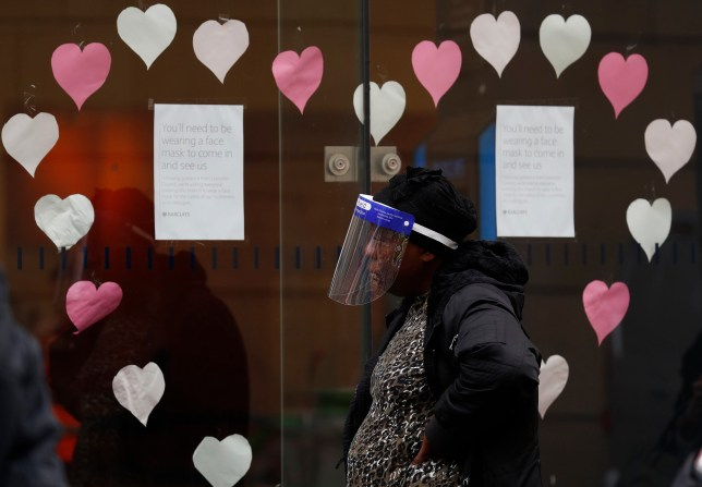 LEICESTER, ENGLAND - JULY 01: A woman wearing a face shield queues outside a Barclays bank on July 01, 2020 in Leicester, England. Ten per cent of all the recent UKs Covid-19 deaths occurred in Leicester, which became the first British city to be put into regional lockdown on Tuesday night. (Photo by Darren Staples/Getty Images)