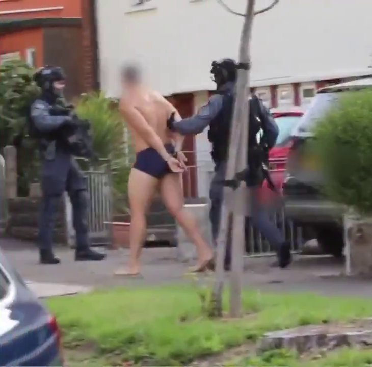 Man in underwear taken away in handcuffs by armed police during Operation Venetic