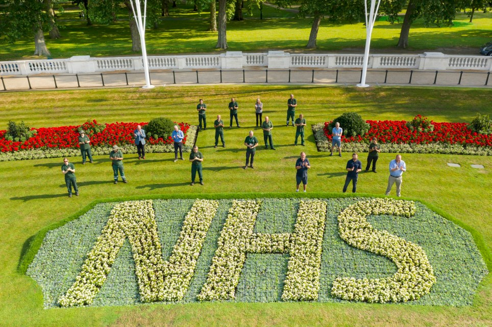Royal Parks staff applaud the NHS's 72 birthday behind one of two specially created 12 x 5 metre flowerbeds in front of Buckingham Palace in the Memorial Gardens in St James's Park. The letters are made up of 1,500 Begonia semperflorens 'Heaven White' plants in each bed, while the background is 21,000 plants of Echeveria imbricate, Senecio serpens and Sedum pachyclados. PA Photo. Issue date: Thursday July 2, 2020. Park Manager Mark Wasilewski believes it's the first change of design to the Memorial Gardens in decades, perhaps since the First World War when the flowerbeds were planted with potatoes. Photo credit should read: The Royal Parks/Greywolf Studios/PA Wire NOTE TO EDITORS: This handout photo may only be used in for editorial reporting purposes for the contemporaneous illustration of events, things or the people in the image or facts mentioned in the caption. Reuse of the picture may require further permission from the copyright holder.