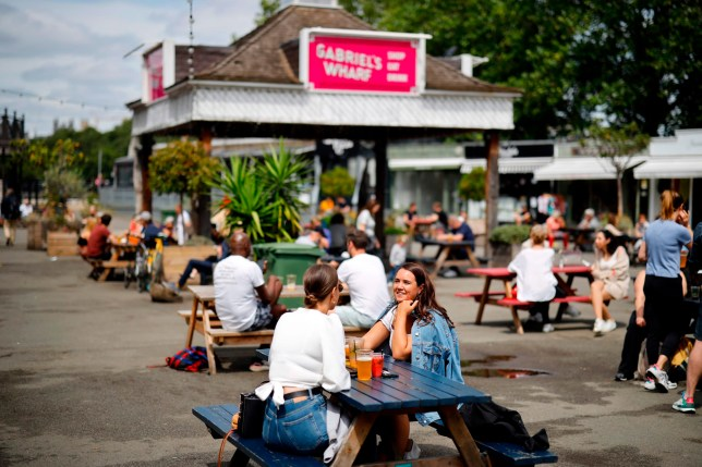 People enjoy a drink at Gabriel's Wharf beside the River Thames in London on July 3, 2020