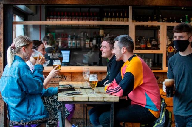 People enjoy a drink inside a bar during  the coronavirus crisis