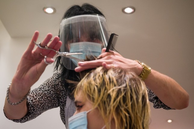 A stylist wears a protective face mask as she cuts a customer's hair at Tusk Hair stylists in Camden just after midnight on July 04, 2020