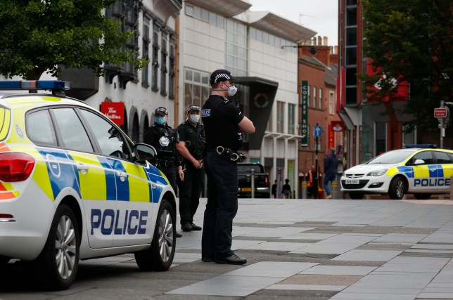 Police officers stand guard in the city centre during local lockdown in Leicester