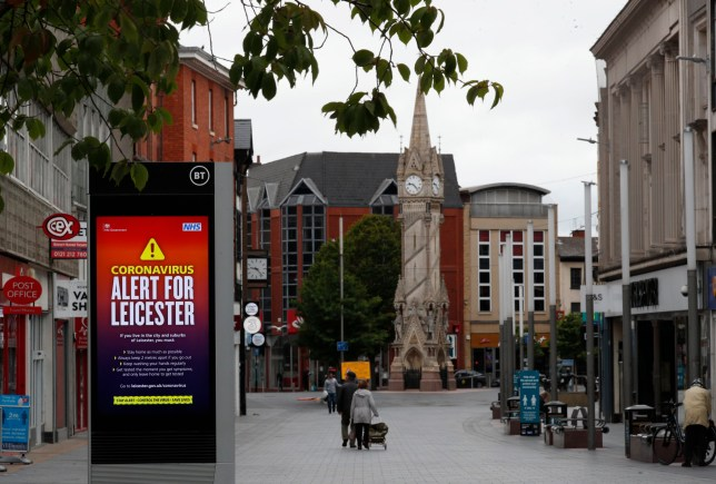 People walk in the city centre during local lockdown on July 04, 2020 in Leicester, England, next to a large Alert sign