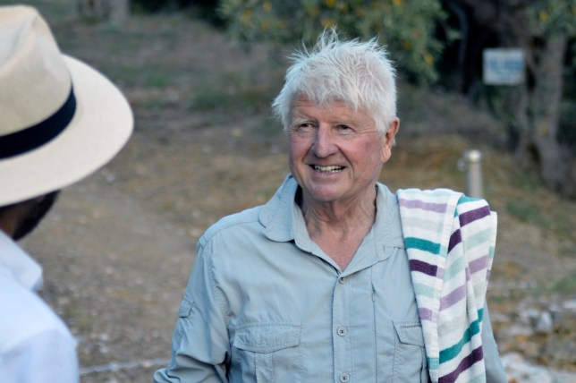 Stanley Johnson, father of Britain's Prime Minister Boris Johnson, speaks with a local reporter, outside his Villa Irene in Horto village, Mount Pelion (also known as Pilio), central Greece, Friday, July 3, 2020. Johnson arrived in Athens on Wednesday evening after flying via Bulgaria due to a current ban on direct flights from the Britain, before visiting his villa on Mount Pelion. (Dimitris Kareklidis/magnesianews.gr via AP)