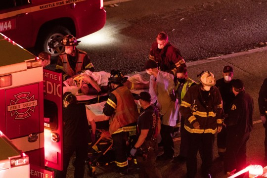 Rescuers bring an injured person into an ambulance after a driver accelerated through a closure linked to the protest on the Interstate 5 freeway in Seattle, authorities said earlier on Saturday, July 4, 2020. Dawit Kelete, 27, he was arrested and booked for two reasons of vehicular assault. (James Anderson via AP)