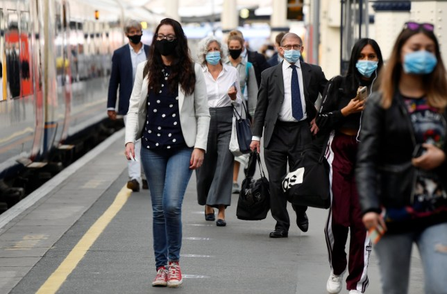 Workers wearing face-masks arrive at Waterloo Station during the morning rush hour