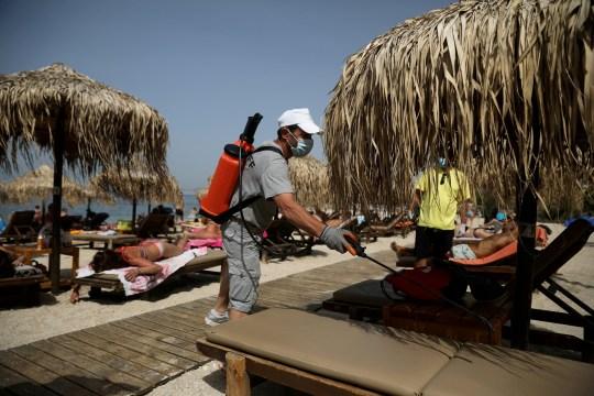 Un homme désinfecte un transat lors de la réouverture officielle des plages au public suite à l'assouplissement des mesures contre la propagation de la maladie à coronavirus (COVID-19), à Athènes, Grèce, le 16 mai 2020.
