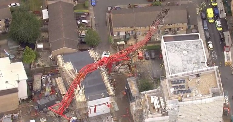 A man has been injured after a 20-metre crane collapsed at a building site in Bow, east London, destroying two houses.