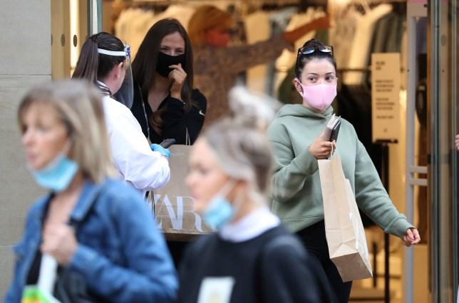 People wear a mask as they leave a shop in Buchanan Street in Glasgow