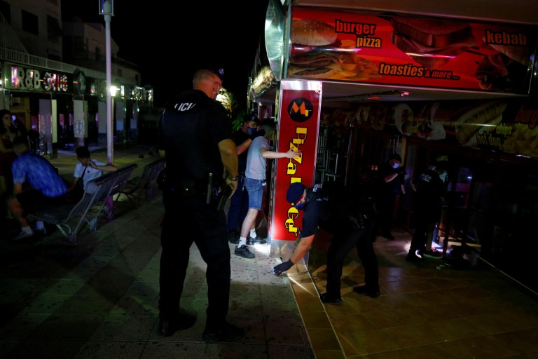 Des policiers portant des masques de protection recherchent de la drogue sur les touristes pendant qu'ils patrouillent dans la rue plus calme de Punta Ballena à Magaluf alors que les bars sont fermés, au milieu de l'épidémie de la maladie à coronavirus (COVID-19), à Majorque, Espagne, le 12 juillet 2020. REUTERS / Enrique Calvo TPX IMAGES DU JOUR