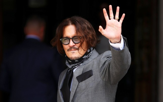 Actor Johnny Depp waves as he arrives at the High Court in London,