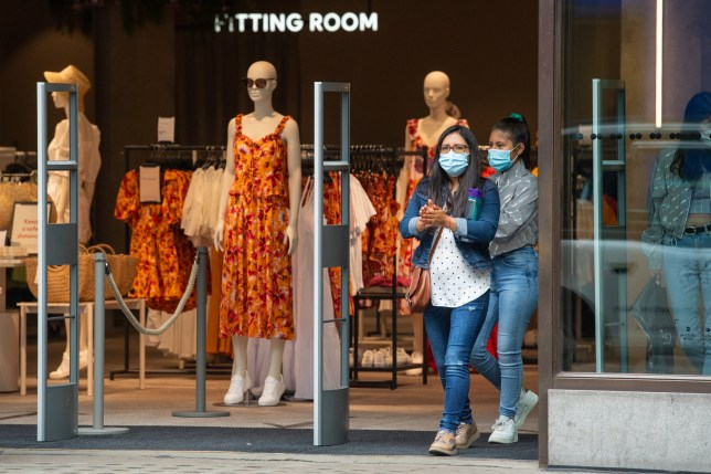 Shoppers wearing face coverings exit a shop on Oxford Street,