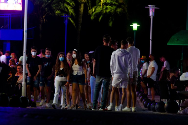 Tourists walk at the street as others stand in a terrace at the resort of Magaluf on the Spanish Balearic island of Mallorca, Spain, Thursday, July 16, 2020. Authorities in Spain's Balearic Islands are pulling the plug on endless drunken nights to the beat of techno music by closing bars and nightclubs in beachfront areas popular with young and foreign visitors. (AP Photo/Francisco Ubilla)