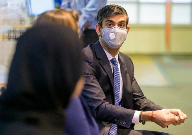 Britain's Chancellor of Exchequer Rishi Sunak wearing a face mask.