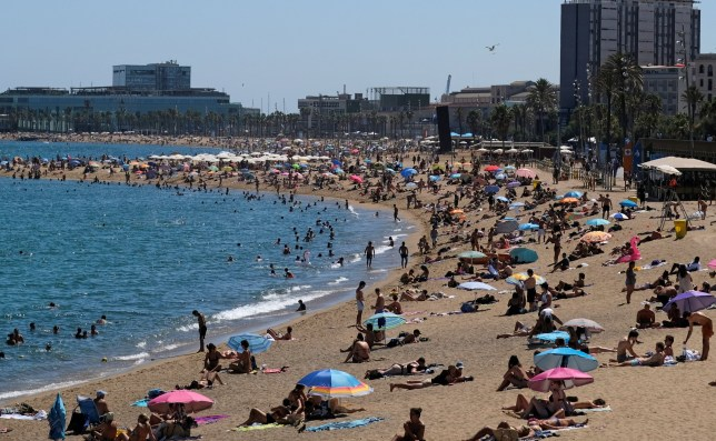 People enjoy the sunny weather at the beach, after Catalonia's regional authorities and the city council announced restrictions to contain the spread of the coronavirus disease