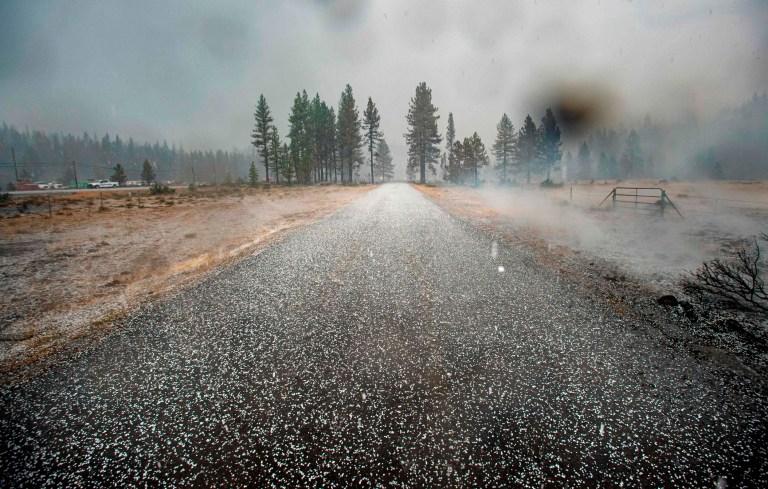 La grêle couvre une route dans une zone encore couvante de l'incendie de Hog près de Susanville, en Californie, le 21 juillet 2020. - Une cellule d'orage mélangée à une colonne de cendres de pyrocumulus du feu de porc, entraînant des vents erratiques et des éclairs avant d'évoluer en un tempête de grêle qui a éteint une partie de l'incendie.